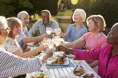 Group Of Senior Friends Making A Toast At Outdoor Dinner Party royalty free stock photography