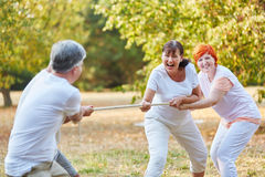 Group of senior friends playing tug of war Royalty Free Stock Images