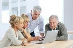 Group of senior friends using laptop Stock Image