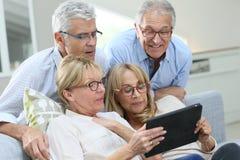 Group of senior friends using tablet having fun stock photo