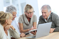 Group of senior friends using tablet and laptop Stock Photo