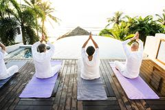 Group of senior friends yoga beside the pool royalty free stock images