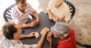 Group Of Senior Men Playing Cards Game In Patio. Happy active retired people, old hispanic friends having fun, seniors playing cards at home Royalty Free Stock Photos