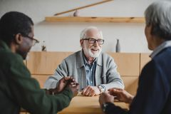 Senior friends sharing stories. Group of senior multiethnic friends sharing stories from past Royalty Free Stock Images