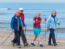 Group of senior nordic walkers on the beach. Kijkduin, The Hague, the Netherlands - May 12 2018: group of senior nordic walkers on the beach Stock Photography