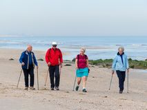 Group of senior nordic walkers on the beach. Kijkduin, The Hague, the Netherlands - May 12 2018: group of senior nordic walkers on the beach Royalty Free Stock Images