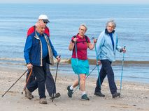 Group of senior nordic walkers on the beach. Kijkduin, The Hague, the Netherlands - May 12 2018: group of senior nordic walkers on the beach Royalty Free Stock Photo