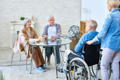 Group of senior people in assisted living home. Nurse entering room with senior men in wheelchair introducing him to patients of assisted living home stock photo
