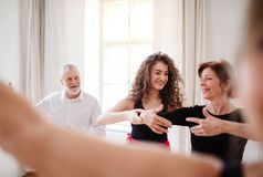 Group of senior people in dancing class with dance teacher. A group of senior people attending dancing class with dance teacher royalty free stock images