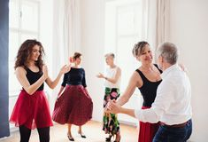 Group of senior people in dancing class with dance teacher. royalty free stock images