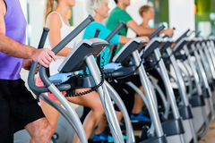Group with senior people on elliptical trainer in gym stock image