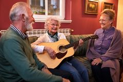 Group of senior people enjoy in friendship at nursing home. While plaing guitar and singing stock image