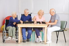 Group of senior people playing rummy game Stock Image