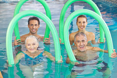 Group of senior people with swim. Noodles in a swimming pool royalty free stock image