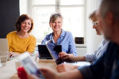 Group of senior people using laptops and tablets in community center club. royalty free stock photo