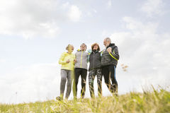 Group of senior runners outdoors, resting, holding around arms. Group of active senior runners outdoors resting, holding around arms Stock Image