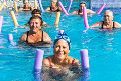 Group of senior women at aqua gym session. Group of active senior women doing aqua gym in outdoor swimming pool Royalty Free Stock Photos