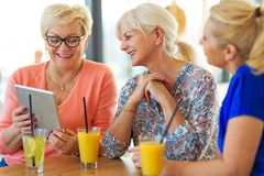 Group of senior women using tablet in a bar Royalty Free Stock Images