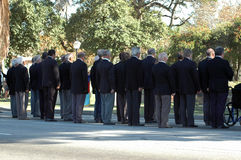 Group of seniors. A group of seniors standing in a row commemorating victims of the second world war outdoors in a park. All old men are wearing suits Stock Photography