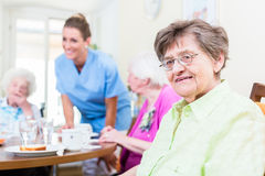 Group of seniors having food in nursing home. A nurse is serving Royalty Free Stock Image
