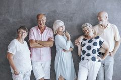 Active seniors fashion statement. Group of seniors leaning against a gray wall wearing casual clothes. Active seniors fashion statement Royalty Free Stock Images