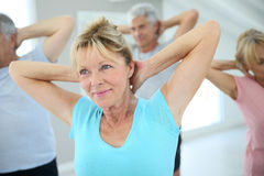 Group of seniors making stretching excercises. Senior people stretching out in fitness room Royalty Free Stock Photos