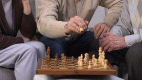 Group of seniors playing chess at nursing home, enjoying leisure time together