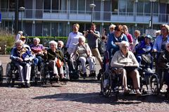Group of seniors in wheelchairs in front of a house for the elderly in Holland royalty free stock photo