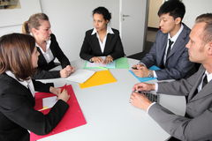 Group of serious business people in a meeting. Group of serious young multiethnic business people in a meeting seated around a table discussing a problem Royalty Free Stock Image