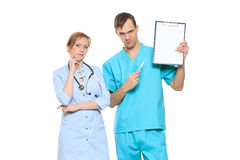 Group serious doctors presenting empty board Royalty Free Stock Photos