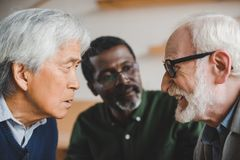 Senior friends playing staring contest. Group of serious multiethnic senior friends playing staring contest Royalty Free Stock Photo