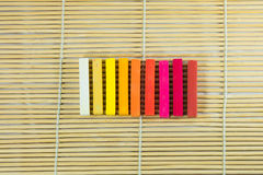 Group set of colored chalk. Group set of warmtone colored chalk on bamboo mat Royalty Free Stock Photo