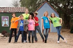Theater camp children pose together. Group of seven happy theater camp friends pose outside in front of set Royalty Free Stock Image