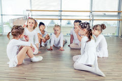 Group of seven little ballerinas sitting on the floor. They are good friend and amazing dance performers Royalty Free Stock Photo