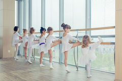 Group of seven little ballerinas standing in row and practicing Stock Photo