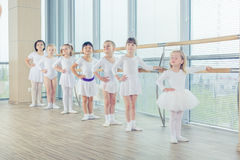 Group of seven little ballerinas standing in row and practicing Royalty Free Stock Photos