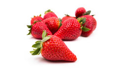 A group of several ripe strawberries. With one in the foreground in focus on a white background Royalty Free Stock Photo