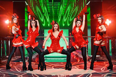 Group of sexy female dancers in red matching outfits performing. Full length portrait of a group of sexy female go-go dancers performing at the disco club Royalty Free Stock Photos