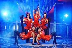 Group of sexy female dancers in red matching outfits performing. Portrait of five beautiful young showgirls posing together at the nightclub with artistic Royalty Free Stock Image