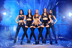 Group of sexy go-go dancers wearing black outfits. Five beautiful young females professional disco club dancers posing on stage at the nightclub performance Royalty Free Stock Image