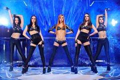 Group of sexy go-go dancers wearing black outfits. Gorgeous young sexy go-go dancers wearing identical black outfits dancing on stage at the night club erotic Stock Photos