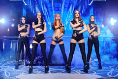 Group of sexy go-go dancers wearing black outfits Stock Images