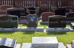 Group of shiny new assorted headstones sitting by the fence Stock Photo