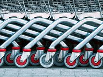Group of shopping carts with red and gray wheels Royalty Free Stock Photos