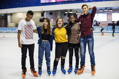 Group shot of teenage friends on the rink ice skating rink royalty free stock images