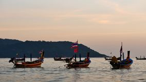 Group of silhouette long tail boat converted floating in the andaman sea with golden light of the Sun. Group of  long tail boat converted to boat excursions stock footage