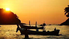 Group of silhouette long tail boat converted floating in the andaman sea with golden light of the Sun. Group of silhouette long tail boat converted to boat stock footage
