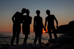 Group silhouette of young people on background of sunset beach and sea. Horizontally framed shot Stock Photography
