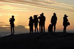 Group of silhouettes watching the sunset in Camps Bay, Cape Town, South Africa royalty free stock images