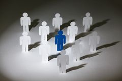 Group of similar paper-men with a blue one Royalty Free Stock Image